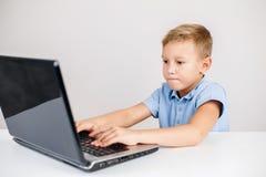 Blonder Junge, der Laptop betrachtet Stockfoto