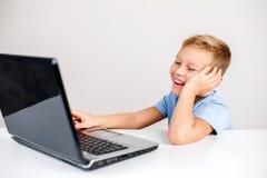 Blonder Junge, der Laptop betrachtet Stockfotografie