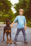 Blonder Junge, der mit dem Hund oder dem Dobermann herein aufwirft Lizenzfreies Stockfoto