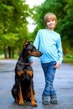 Blonder Junge, der mit dem Hund oder dem Dobermann herein aufwirft Lizenzfreie Stockfotos