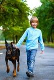 Blonder Junge, der mit dem Hund oder dem Dobermann herein geht Lizenzfreies Stockbild