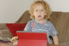 Blonder Junge, der mit einer digitalen Tablette spielt Stockbild