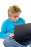 Blonder Junge, der mit Laptop arbeitet Lizenzfreie Stockbilder
