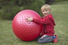 Blonder Junge, der mit rotem entspannendem Ballon spielt Lizenzfreie Stockfotos