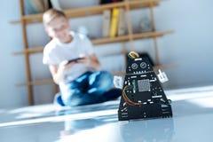 Blonder Junge, der sein neues Roboterspielzeug prüft Stockbild