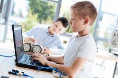 Blonder Junge, der seinen neuen Roboter programmiert Stockfoto
