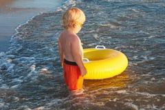Blonder Junge in der Sonnenbrille mit aufblasbarem Ring auf dem Seestrand Lizenzfreies Stockbild