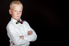 Blonder Junge in der weißen Hemd- und Regenbogenfliege Stockfotografie