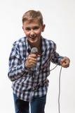 Blonder Junge des emotionalen Sängers in einem karierten Hemd mit einem Mikrofon Lizenzfreies Stockbild