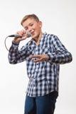 Blonder Junge des emotionalen Sängers in einem karierten Hemd mit einem Mikrofon Stockfoto