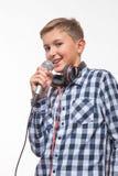 Blonder Junge des emotionalen Sängers in einem karierten Hemd mit einem Mikrofon und Kopfhörern Lizenzfreies Stockfoto