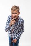 Blonder Junge des emotionalen Sängers in einem karierten Hemd mit einem Mikrofon und Kopfhörern lizenzfreie stockbilder