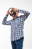 Blonder Junge des emotionalen Sängers in einem karierten Hemd mit Kopfhörern Lizenzfreies Stockfoto