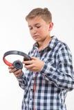 Blonder Junge des emotionalen Sängers in einem karierten Hemd mit Kopfhörern Stockfoto