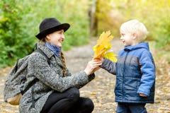 Blonder Junge gibt seiner Mutter einen Blumenstrauß von gelben Blättern Herbst FO Lizenzfreie Stockfotos