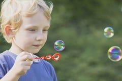 Blonder Junge im blauen Hemd brennt Luftblasen durch Stockfotografie