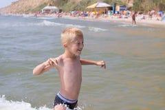 Blonder Junge im Meer Stockbilder
