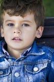 Blonder Junge im sonnigen Park, der Kamera betrachtet Stockbild