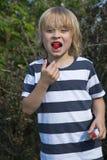 Blonder Junge isst Erdbeere Lizenzfreie Stockbilder