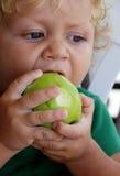 Blonder Junge isst grünen Apfel Stockfoto