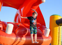 Blonder Junge (7-9 Jahre) springend in federnd Schloss Lizenzfreies Stockfoto