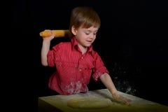 Blonder Junge knetet den Teig, der mit Mehl geschmiert wird Stockfoto