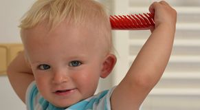 Blonder Junge lernt, sich zu kämmen Stockbilder