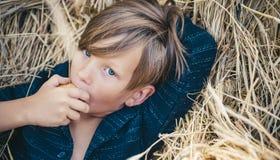 Blonder Junge liegt auf Heuhintergrund und isst einen Apfel Der Junge annonciert Kind-` s Kleidung w?hrend des Herbstes gl?cklich lizenzfreie stockbilder
