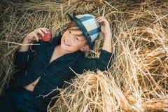 Blonder Junge liegt auf Heuhintergrund und isst einen Apfel Verkauf f?r gesamte Herbstkollektion, unglaubliche Rabatte lizenzfreie stockbilder