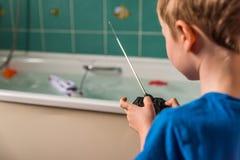 Blonder Junge mit britischer Flagge auf dem blauen T-Shirt, das mit kontrolliertem Radioboot im Badezimmer spielt Stockfoto