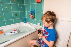 Blonder Junge mit britischer Flagge auf dem blauen T-Shirt, das mit kontrolliertem Radioboot im Badezimmer spielt Stockfotos