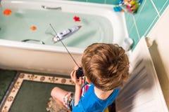 Blonder Junge mit britischer Flagge auf dem blauen T-Shirt, das mit kontrolliertem Radioboot im Badezimmer spielt Stockfotografie