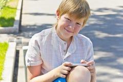 Blonder Junge mit dem Handy, der auf einer Bank sitzt Stockbilder