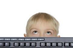 Blonder Junge mit der Tastatur, die oben schaut Lizenzfreies Stockbild