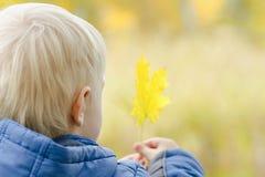 Blonder Junge mit einem gelben Blatt in seiner Hand Hintere Ansicht, Nahaufnahme Stockbilder