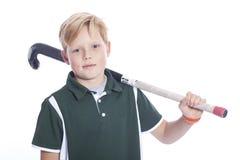 Blonder Junge mit Hockeystock im Studio Stockbild
