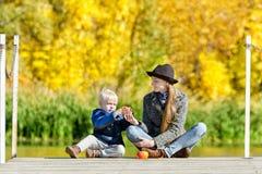 Blonder Junge mit seiner Mutter, die auf dem Dock sitzt und mit a spielt Lizenzfreies Stockfoto