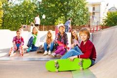 Blonder Junge mit Skateboard und seine Kameraden sitzen hinten Stockfotos