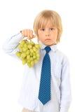 Blonder Junge und grüne Trauben Stockbild