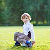 Blonder Junge von 4 liegend beim Fußball auf Fußballplatz Stockfoto