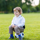 Blonder Junge von 4 liegend beim Fußball auf Fußballplatz Stockbilder