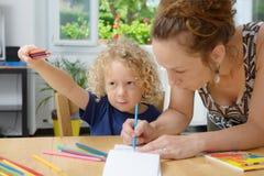 Blonder Junge zeichnet mit seiner Mutter Lizenzfreies Stockfoto