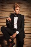 Blonder junger eleganter Mann, der auf einem Stuhl sitzt Lizenzfreies Stockbild