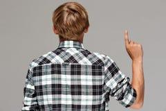 Blonder junger Mann, der das zufällige karierte Hemd steht zurück zu der Kamera, oben zeigend mit dem Finger über grauem Hintergr Stockbild