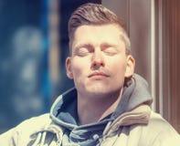 Blonder junger Mann, der die Sonne genießt Lizenzfreies Stockbild