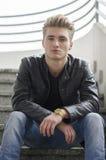 Blonder junger Mann, der draußen auf Treppe sitzt Stockfotografie