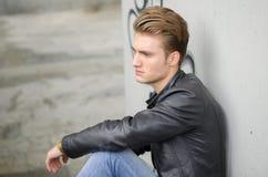 Blonder junger Mann, der draußen auf Treppe sitzt Stockfotos