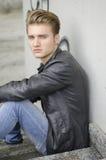 Blonder junger Mann, der draußen auf Treppe sitzt Lizenzfreie Stockbilder