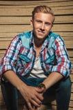 Blonder junger Mann, der im Studio beim Lächeln sitzt Lizenzfreies Stockfoto