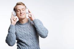 Blonder junger Mann, der Musik in den Kopfhörern hört Stockfotos